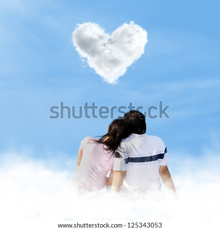 Asian couple enjoying the beautiful love shape clouds under blue sky