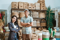 asian couple entrepreneur with crossed hands while in a craft shop with handmade crafts on the shelf background