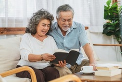 Asian couple Grandparent sitting and reading the book together with happy feeling in house, Long live and Elderly society, Warm family and happiness, covid19 outbreak and social distancing concept