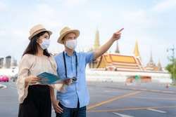 Asian couple happy tourists to travel wearing mask to protect from Covid-19 on they holidays and holding travel map and pointing in Wat Phra Kaew Temple in Bangkok, Thailand