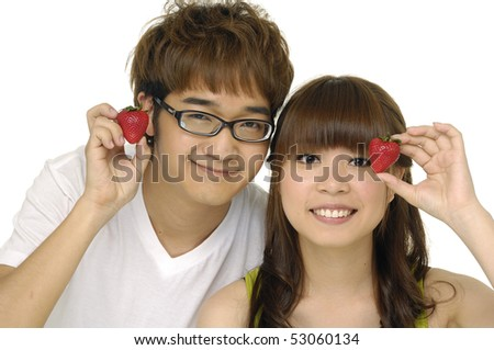 Asian couple holding strawberries - stock photo