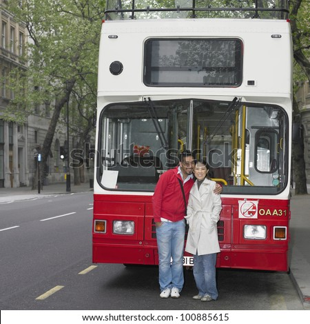 Asian couple hugging in front of tour bus in London