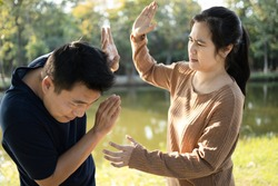 Asian couple,husband afraid to his wife,woman swings to hit fighting a man,female people slapping,threatening scared man, male trying protect himself by raising hand guarding her,conflict,argument