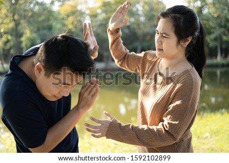 Photo of  Asian couple,husband afraid to his wife,woman swings to hit fighting a man,female people slapping,threatening scared man, male trying protect himself by raising hand guarding her,conflict,argument
