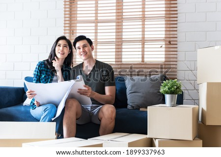 Asian couple, Husband and attractive wife looking and discuss about renovating the old house to be new home, to people, Real estate and renovation concept.