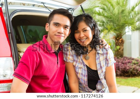 Asian couple is happy in front the car and ready to go on vacation