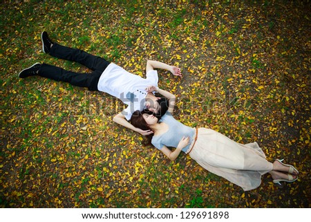Asian couple laying down outdoor in park looking happy on fall ground