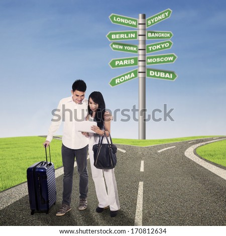 Asian couple looking direction on a digital tablet with road signs background, shot outdoor