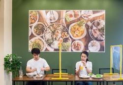 Asian couple man and woman sitting in restaurant eating food with table shield to protect infection from coronavirus covid-19, restaurant and social distancing concept
