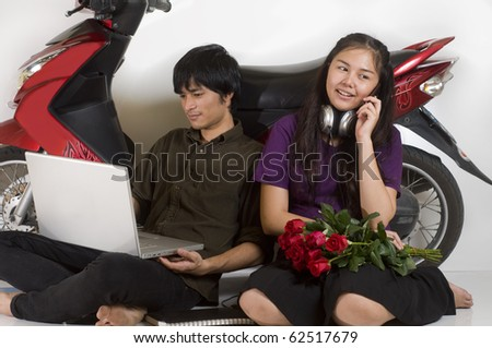 Asian couple relaxing next to motor scooter