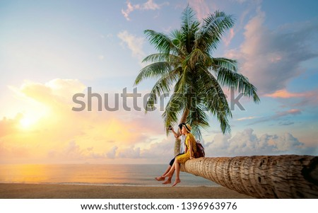 Asian couple selfie by camera on coconut palm tree in Kho Mak island, Kood, Trat, Thailand, this image can use for summer, beach, travel and valentine concept #1396963976