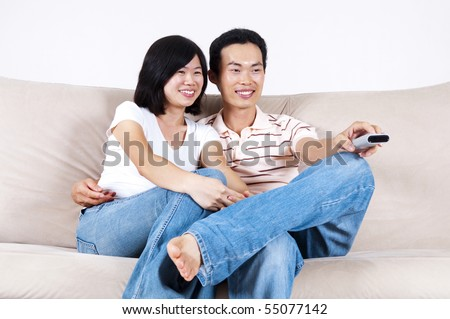 Asian couple sitting on sofa watching TV together.