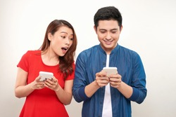 Asian couple using gadgets: pretty girl typing a message on cell phone while her boyfriend standing next to her, looking down at the screen of her smart phone