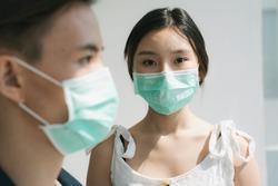 Asian couple wearing doctor mask staying inside the house. Asian wife concern about her husband to go outside and work. Sideview of a man wearing doct mask for foreground.