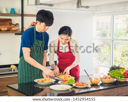 Asian couple young man and girl are cooking so enjoy in free time.