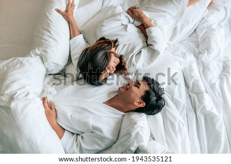 Asian couples is laying on bed in the bed room at modern home.Couple in Valentine day.Love couple,Relationship and couple concept.