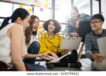 Asian creative team sitting and working sharing creative ideas inspire in workshop together. Business people are meeting at creative office workplace.