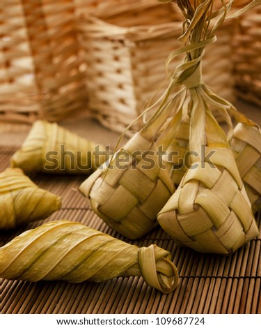 Asian cuisine ketupat or packed rice in low light setting. - stock photo