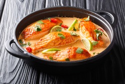 Asian cuisine. Salmon with coconut sauce, lime and herbs close-up in a frying pan on the table. horizontal
