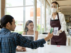 Asian customer scan QR code online menu from waitress with face mask and face shield. Customer sat on social distancing table for new normal lifestyle in restaurant after coronavirus covid-19 pandemic