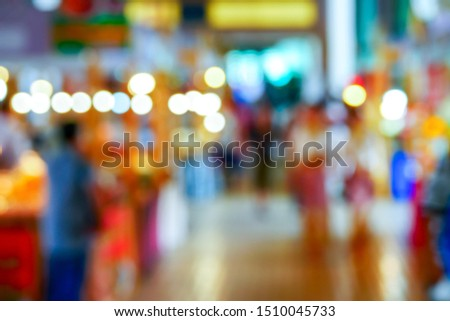 Asian customer walking and buy a souvenir product or food from a merchant at a boot of street market of an indoor exhibition,Thailand,with a blur focus
