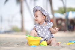 Asian cute baby girl playing on the sand beach on sunny day