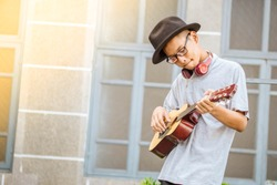 Asian cute boy freedom lifestyle smile practicing playing acoustic guitar music skills on street outdoor background city view have copy space ,Concept of a musician's career concert and young talents