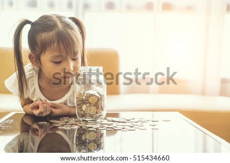 asian cute girl saving money putting coins into glass bank, vintage tone