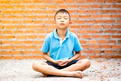 Asian cute kid sitting meditation on ground on brick wall background. Child boy thinking and brain gym. He focusing mind on a head to achieve a mentally clear and emotionally calm state