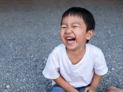 Asian cute little child boy laughing with mouth open wide, seeing whitening teeth. Happy Kid in white shirt enjoy in funny shot in relaxing day.