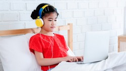 Asian Cute little girl wear headphones to learn online using a laptop. Is a Homeschool. Studying in the bedroom with a good environment. And Corinavirus Prevention (COVID-19). Concept education