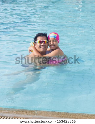 Asian dad and daughter in the swimming pool