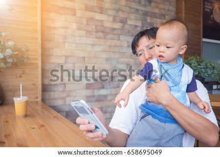 Asian Dad and son sitting in a city cafe look in the phone, Father holding Cute little Asian 1 year old toddler baby boy child at the restaurant, leisure & technology & internet addiction concept