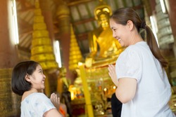 Asian daughter and mother making worship to the Buddha statue in temple