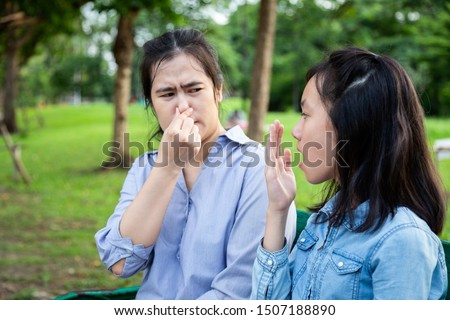 Asian daughter child girl checking breath with her hand,teen girl horrible bad breath,foul mouth,mother closing her nose,very bad smell,feeling stinks,facial expression,health care,halitosis concept