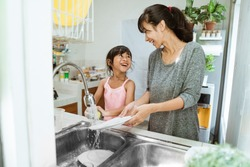 asian Daughter helping her mother in the kitchen washing dishes together