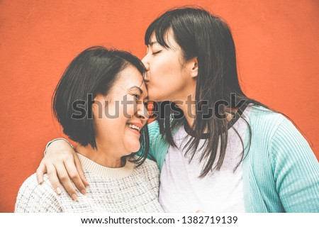 Asian daughter kissing mum on mother day - Happy family people enjoying time togehter - Love, motherhood lifestyle, tender moments concept - Focus on faces #1382719139