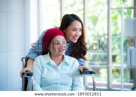 Asian daughter stand closely to her mother who sitting on wheelchair and wearing red headscarf smiling and looking through window with feeling happy.  Cancer or leukemia survivor concept.