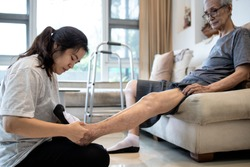 Asian daughter taking care of helping elderly,woman wear socks on feet of her senior mother,old people with cold toes,numb in foot,sensitivity to cold,putting on socks to warm up,health care at home