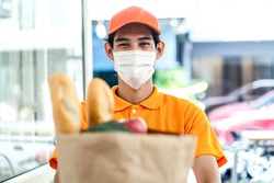 Asian deliver man wearing face mask in orange uniform holding bag of food, groceries, fruit standing in front of customer home. Postman and express grocery delivery service during covid19 pandemic.
