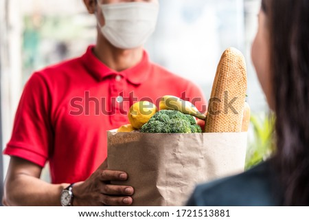 Asian deliver man wearing face mask in red uniform handling bag of food, fruit, vegetable give to female costumer in front of the house. Postman and express grocery delivery service during covid19.