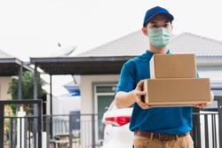 Asian delivery express courier young man giving boxes to woman customer he wearing protective face mask at front home, under curfew quarantine pandemic coronavirus COVID-19