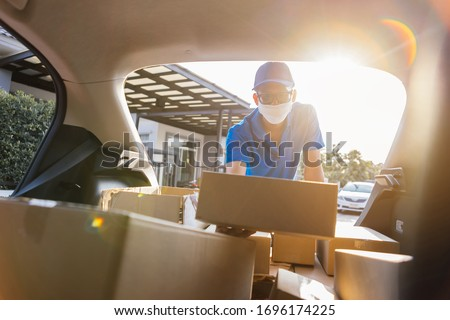Asian Delivery man wearing mask picking up the package on front receiver shipping deliver cargo social distancing, Many parcel in trunk hatchback car while the virus is spreading at sunset.