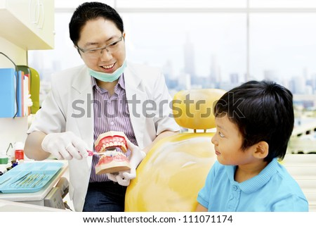 Asian dentist showing a boy  how to brush his teeth properly