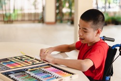 Asian disabled child on wheelchair coloring art work,The skills to practice muscle development,Special children's lifestyle,Life in the education age of special need kids,Happy disability kid concept.