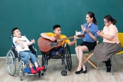 asian disabled children and woman teacher enjoying and playing guitar
