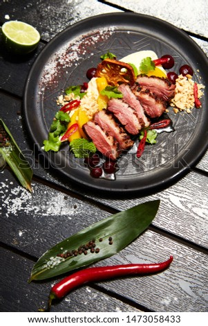 Asian dish on a black plate on a wooden table decorated with lime, pepper, salt, chili and flour. Appetizing roasted duck breast with peach. Restaurant serving #1473058433