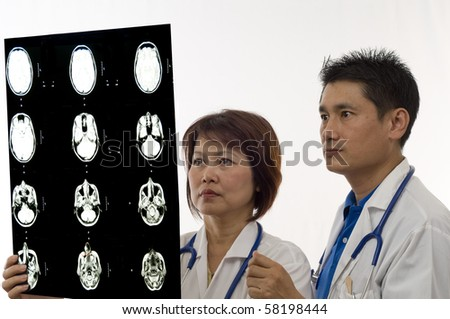 Asian Doctor and Nurse looking at patients MRI or x-ray