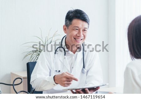 Asian doctor and patient are discussing something while sitting at the table