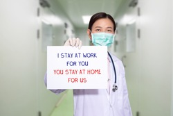 Asian doctor at hospital wear medical masks, holding paper with text I STAY AT WORK FOR YOU, YOU STAY AT HOME FOR US. stay at home policy campaign to control COVID-19 Coronavirus outbreak situation